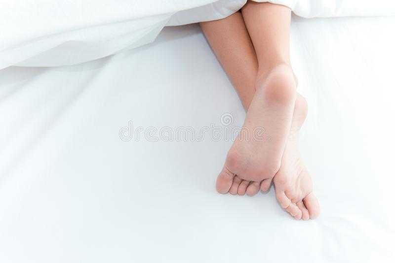 Woman feet on the bed under white blanket. Sleeping and relax concept. Vacation and Holiday theme.  stock image