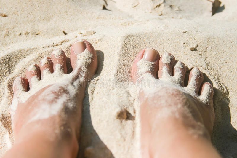 Woman feet covered with white sand at the beach royalty free stock photo