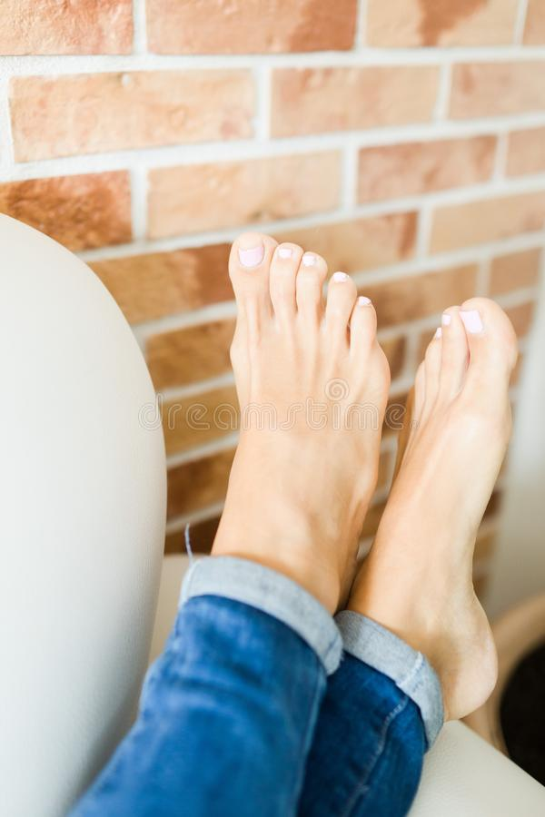Woman feet in details, bare feet in comfortable position. On sofa near brick wall stock images