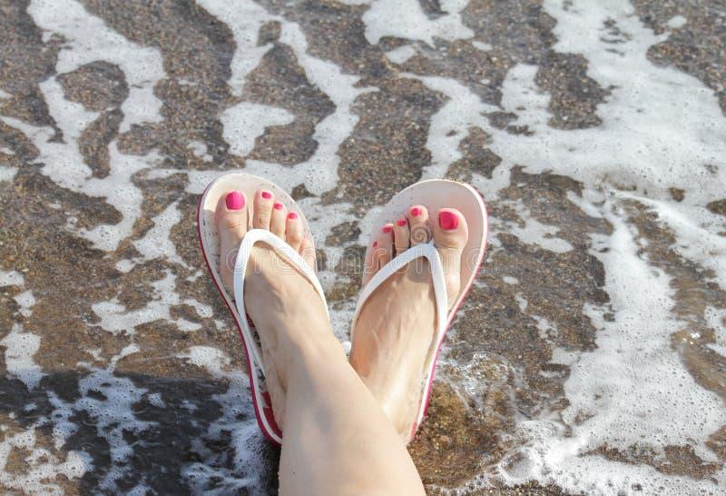 Woman Feet with flip flops on the Beach
