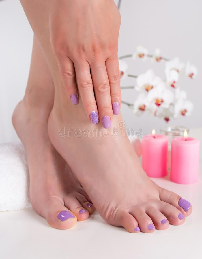 Woman feet and hands with lilac nails polish color stock photo