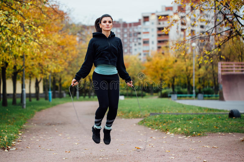 Woman feet jumping, using skipping rope in park. Beautiful brunette sportsgirl doing cardio exercises royalty free stock images