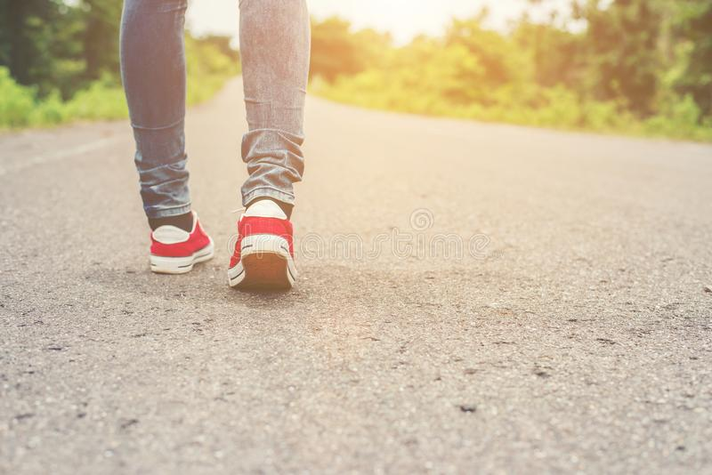Woman feet with red sneaker shoes walking on the roadside. Woman feet with red sneaker shoes walking on the roadside background royalty free stock photo