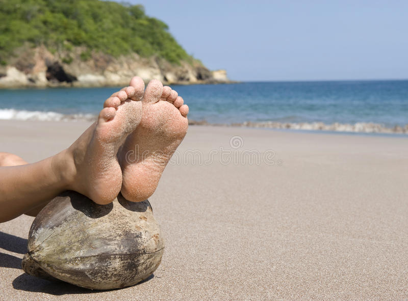 Woman feet resting coconut beach, costa rica stock images