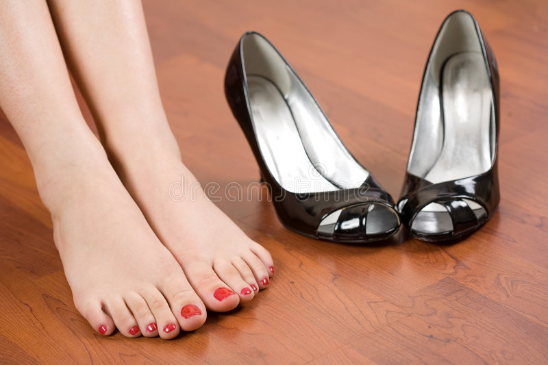 Woman feet and shoes. Woman feet with shoes nearby royalty free stock image