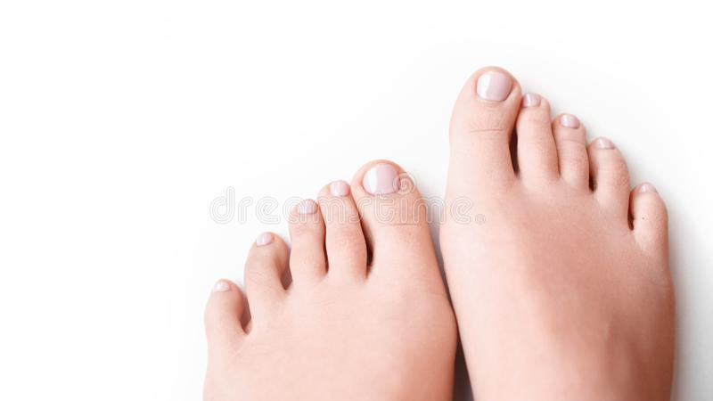 Woman feet with soft pink manicure isolated on white royalty free stock image