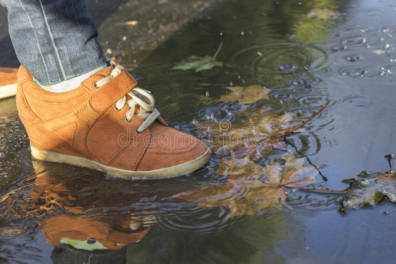 Woman feet walking in a puddle in orange boots.  stock images