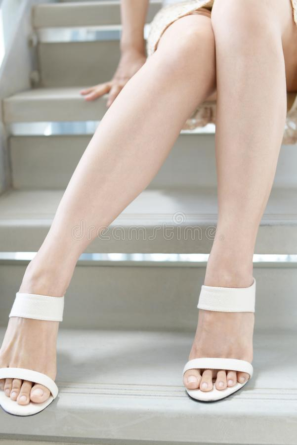 Woman legs in fashionable high heel sandals. Woman feet wearing white heel sandals royalty free stock image