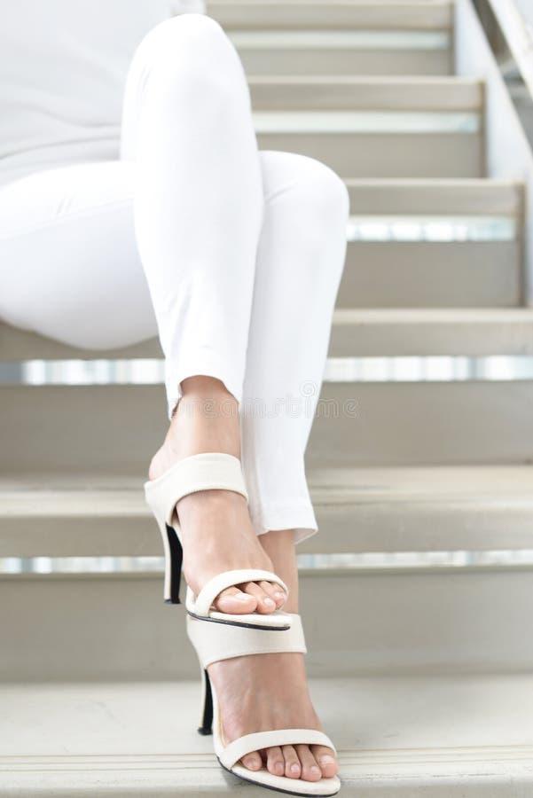 Woman legs in fashionable high heel sandals. Woman feet wearing white heel sandals stock photos