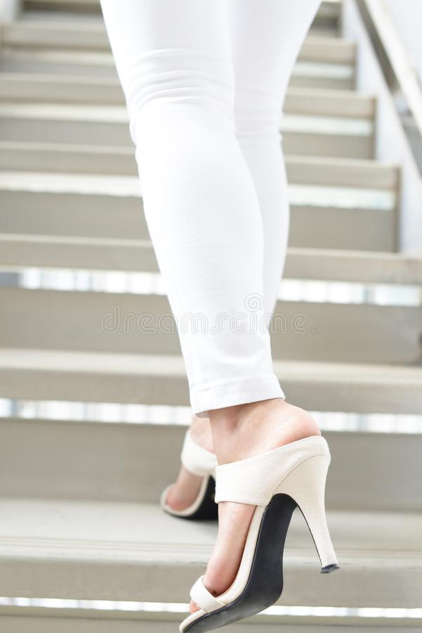 Woman legs in fashionable high heel sandals. Woman feet wearing white heel sandals royalty free stock photos