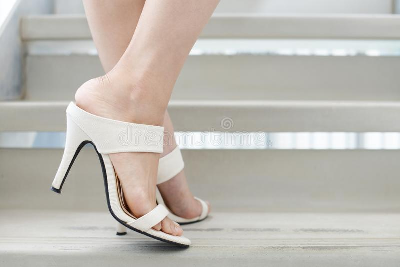 Woman legs in fashionable high heel sandals. Woman feet wearing white heel sandals royalty free stock photography