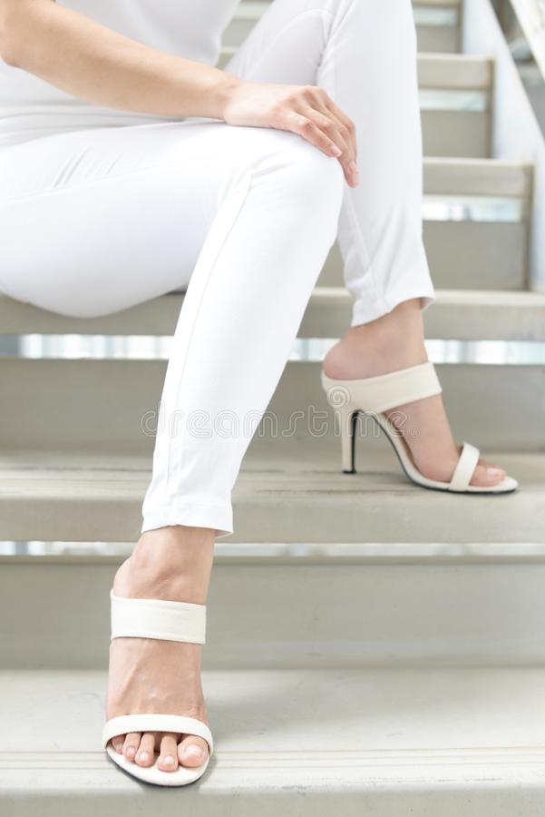 Woman legs in fashionable high heel sandals. Woman feet wearing white heel sandals royalty free stock images