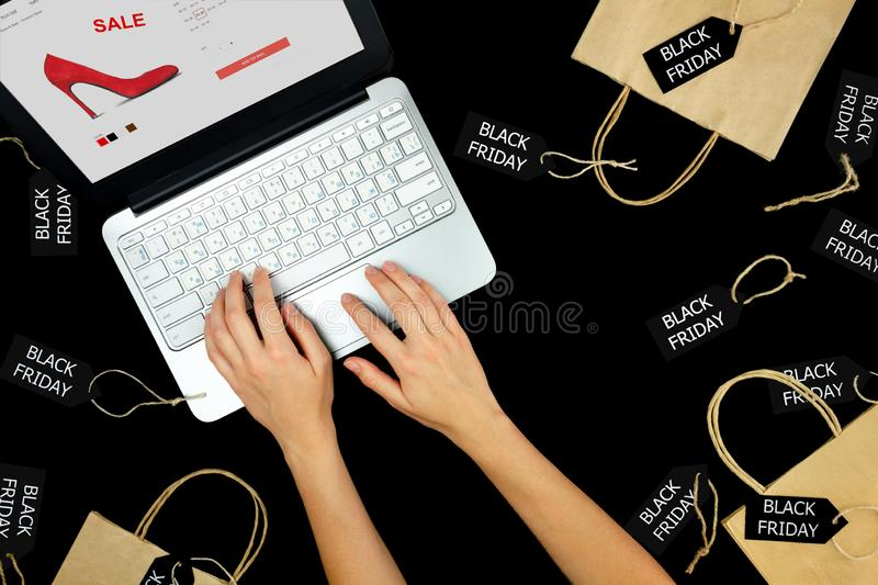 Woman female adult hands with laptop purchasing buying new red high heels with sale discount in internet online shop store during stock photography
