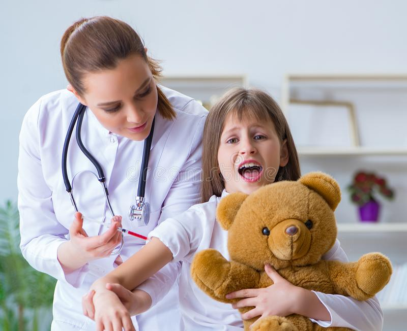 Woman female doctor examining little cute girl with toy bear. The women female doctor examining little cute girl with toy bear stock photo