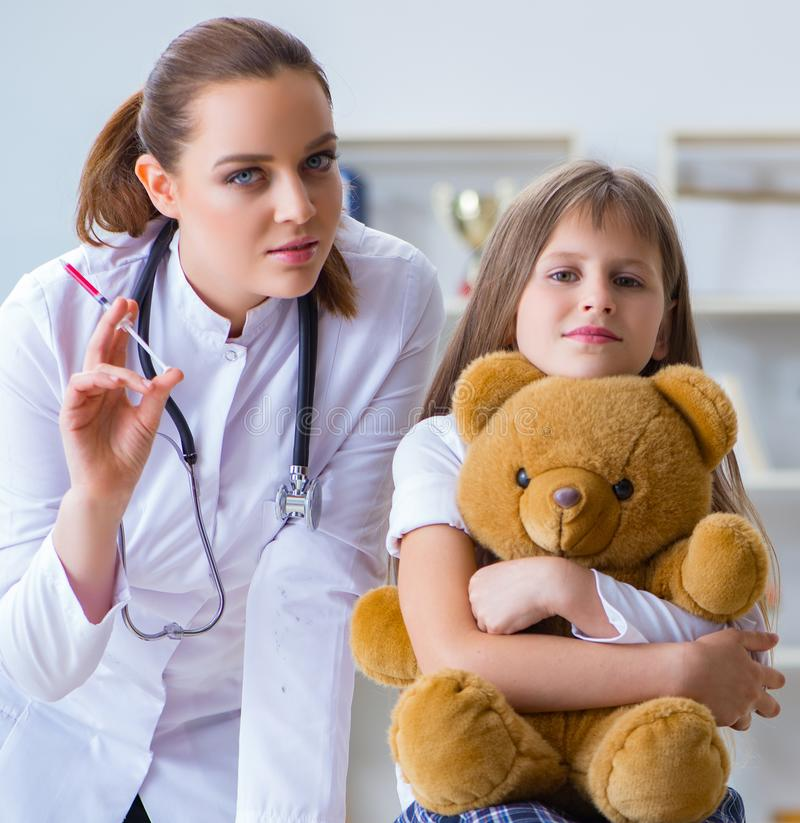 Woman female doctor examining little cute girl with toy bear. The women female doctor examining little cute girl with toy bear royalty free stock photo