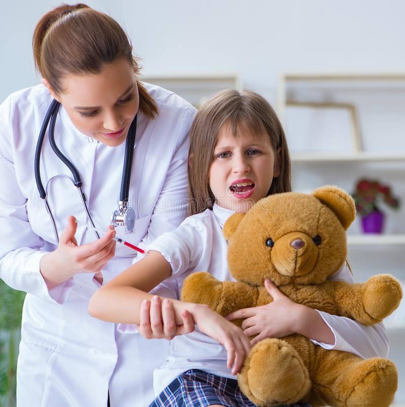 Woman female doctor examining little cute girl with toy bear. The women female doctor examining little cute girl with toy bear stock photos