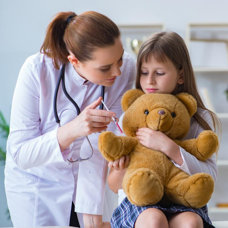 Woman female doctor examining little cute girl with toy bear. The woman female doctor examining little cute girl with toy bear royalty free stock image