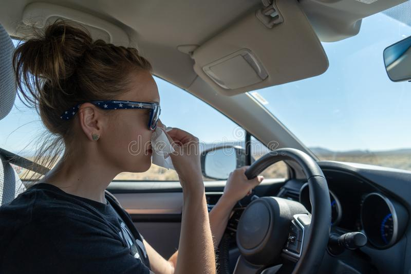 Woman female driver uses a tissue to blow her nose while driving. Concept for distracted driving, multi tasking, health issues,. Colds, sick, medical issues stock photos