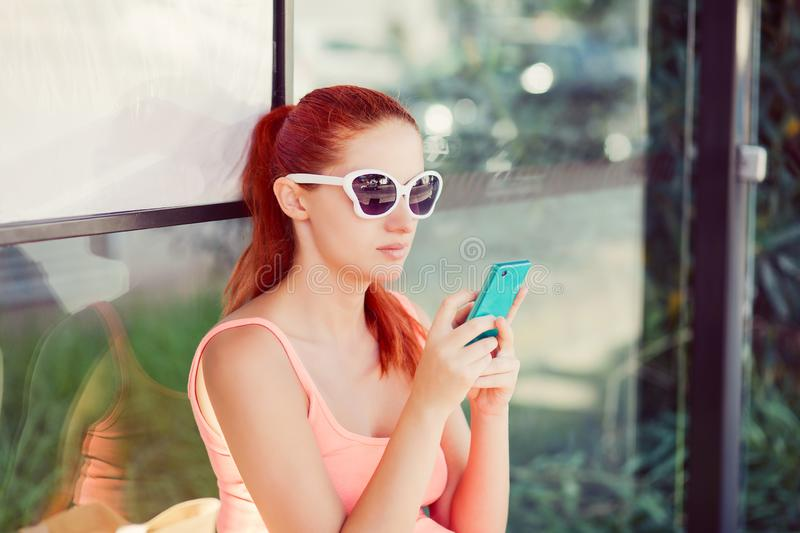 Woman female girl sitting in a bus station using application on smartphone for calling taxi stock photos