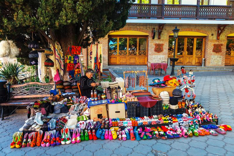 Woman female vendor sells and knits woolen slippers and socks in Sighnaghi town, Kakheti region, Georgia. Signagi, Georgia - 20 April, 2017: Woman female vendor royalty free stock photo