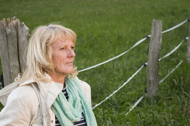 Woman at the fence look away royalty free stock image