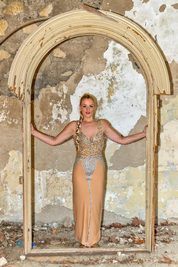 A woman in a festive dress in an abandoned castle. The female model poses next to the abandoned door. A woman in a festive dress in an abandoned castle. The stock image