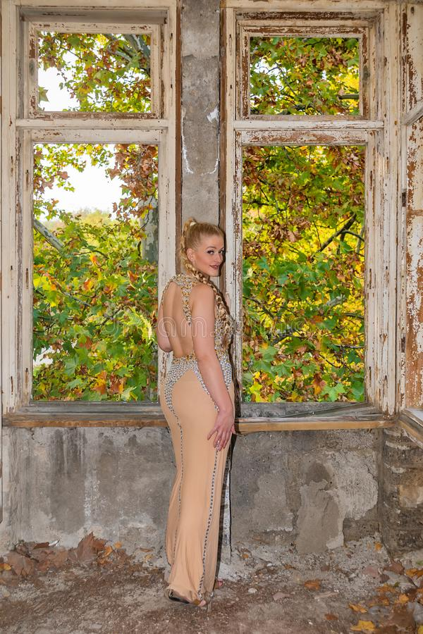 A woman in a festive dress in an abandoned castle. The female model poses next to the abandoned door. A woman in a festive dress in an abandoned castle. The royalty free stock photo