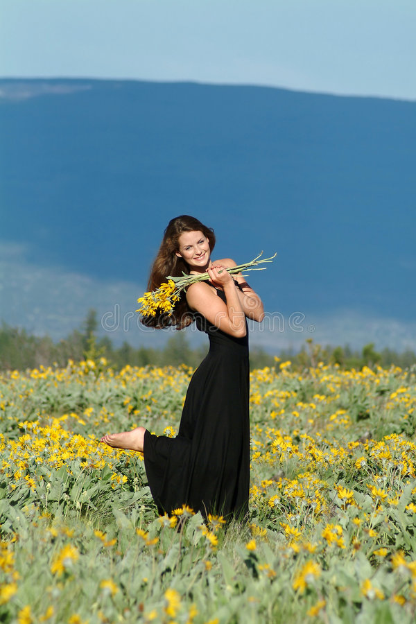 Woman in field of flowers. Woman wearing black dress standing in field of flowers royalty free stock images