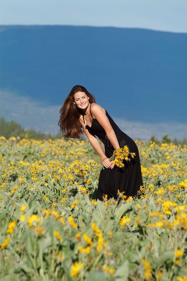 Woman in field of flowers. Woman wearing black dress standing in field of flowers stock photo
