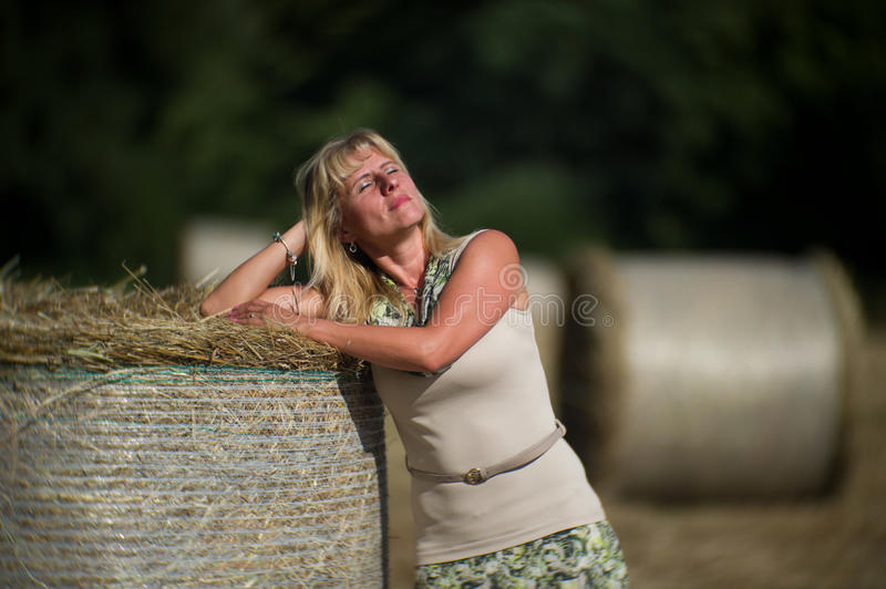 Woman on the field - straw bales. Nice woman on the field, late afternoon royalty free stock photography
