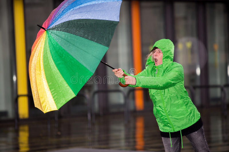 Woman fighting against rain and wind stock image