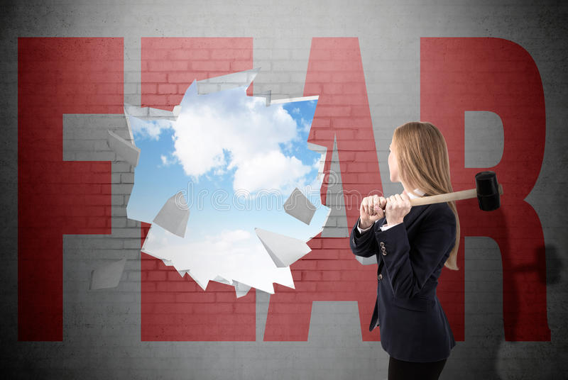 Woman fights her fears. Woman has crashed a white brick wall with sledgehammer and word fear written on it. Sky is seen through the hole. Concept of conquering stock photo