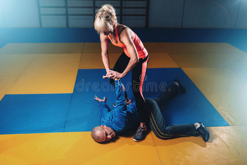 Woman fights with man, self-defense technique. Self defense workout in gym, martial art stock images