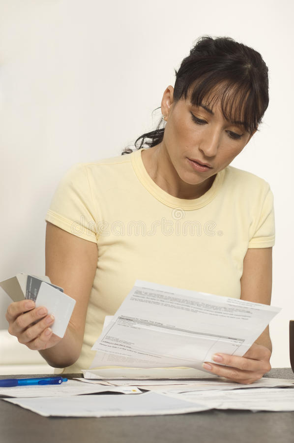 Woman Figuring Out Bills. At desk royalty free stock photos
