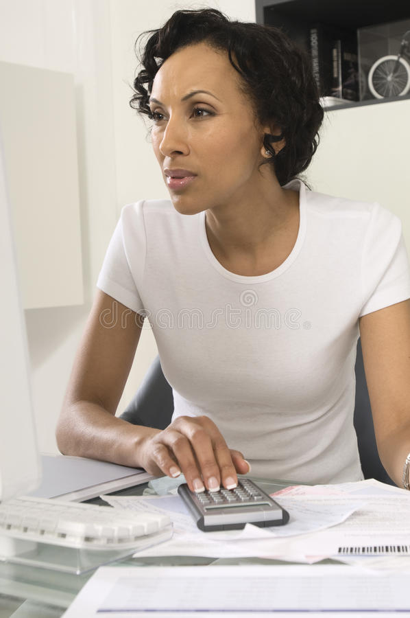 Woman Figuring Out Personal Finances. An African American woman figuring out personal finances at home stock image