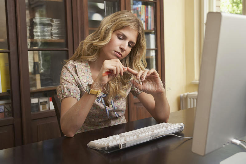 Download Woman Filing Fingernails Over Computer In Study Room Stock Photo - Image: 33893014