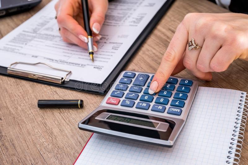 Woman filing individual income tax form 1040. With calculator. close up royalty free stock photos