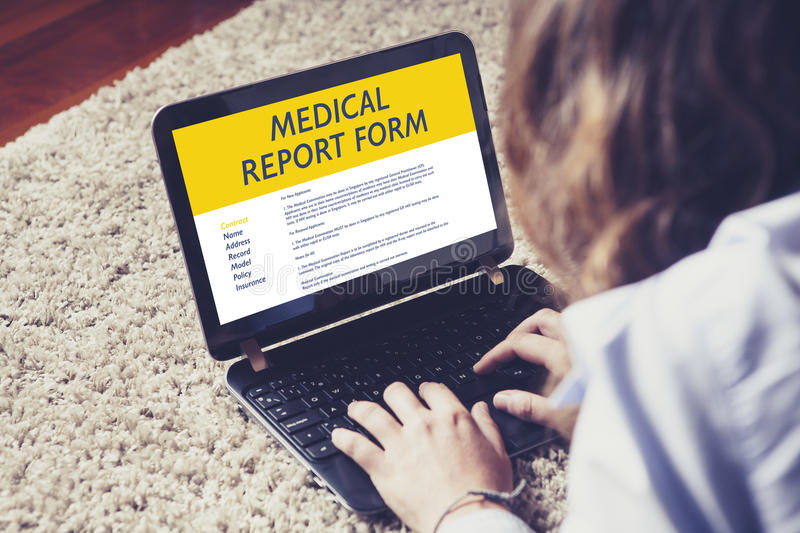 Woman fill in a Medical report form in a laptop. royalty free stock photography