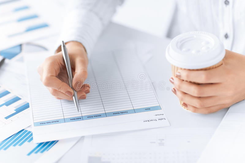 Woman filling in form and drinking coffee. Picture of woman hand filling in blank paper and drinking coffee royalty free stock images