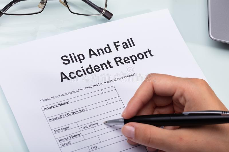 Woman Filling Slip And Fall Accident Report. Close-up Of A Woman`s Hand Filling Slip And Fall Accident Report stock photos
