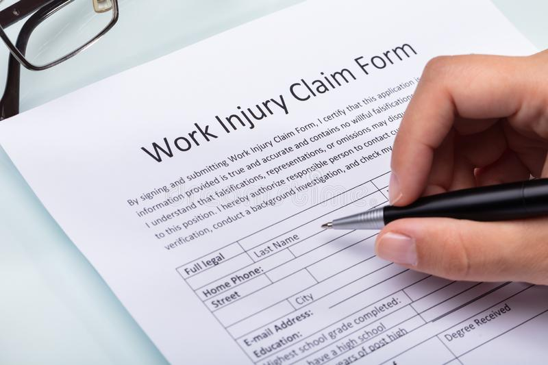 Woman Filling Work Injury Claim Form stock photography