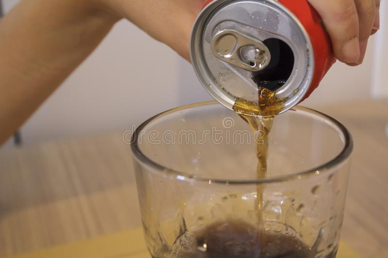 Woman fills the glass with cola royalty free stock photo
