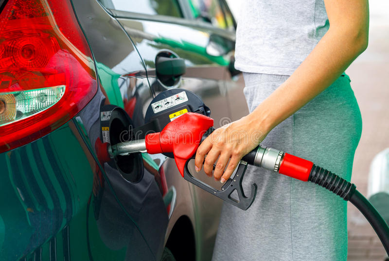 Woman fills petrol into the car at a gas station royalty free stock photography