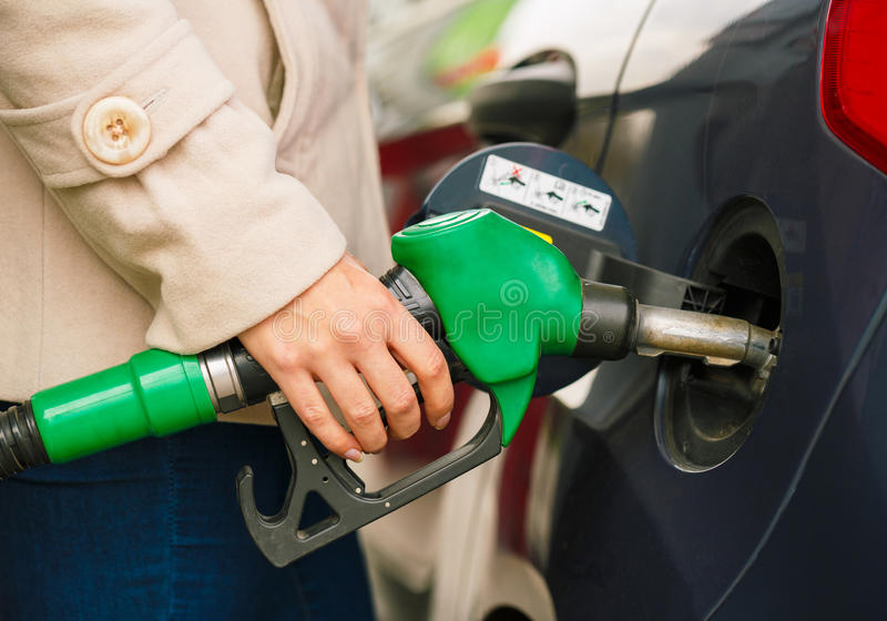 Woman fills petrol into her car at a gas station royalty free stock photography