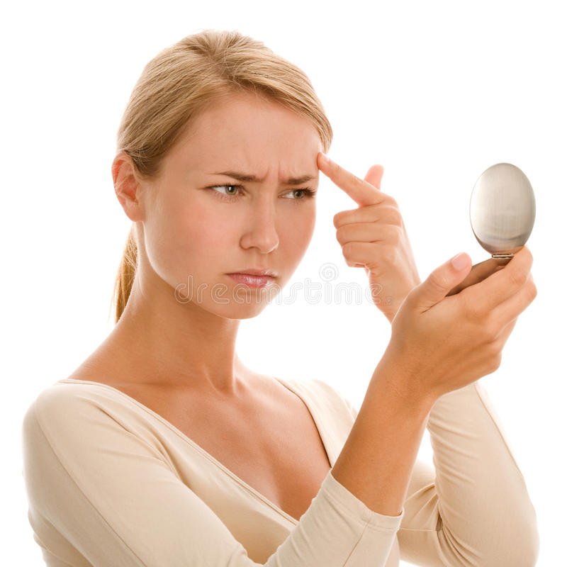 Woman finding an acne. On her forehead stock image