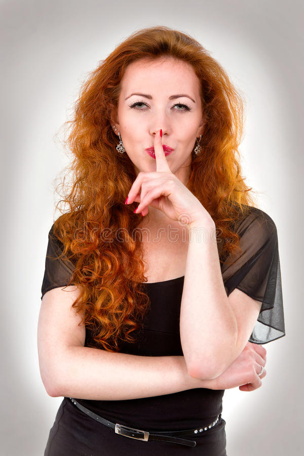 Woman with finger over mouth royalty free stock photo