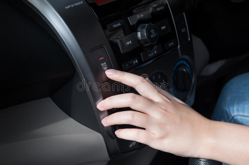 Woman finger pressing button defrost detail on a car`s dashboard. Shallow DOF car interior royalty free stock photos