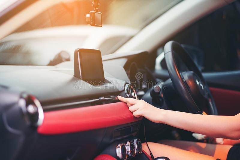 Woman finger pressing emergency button on car dashboard. Transportation Concept, The female hand presses the button to turn the. Alarm into the car stock images