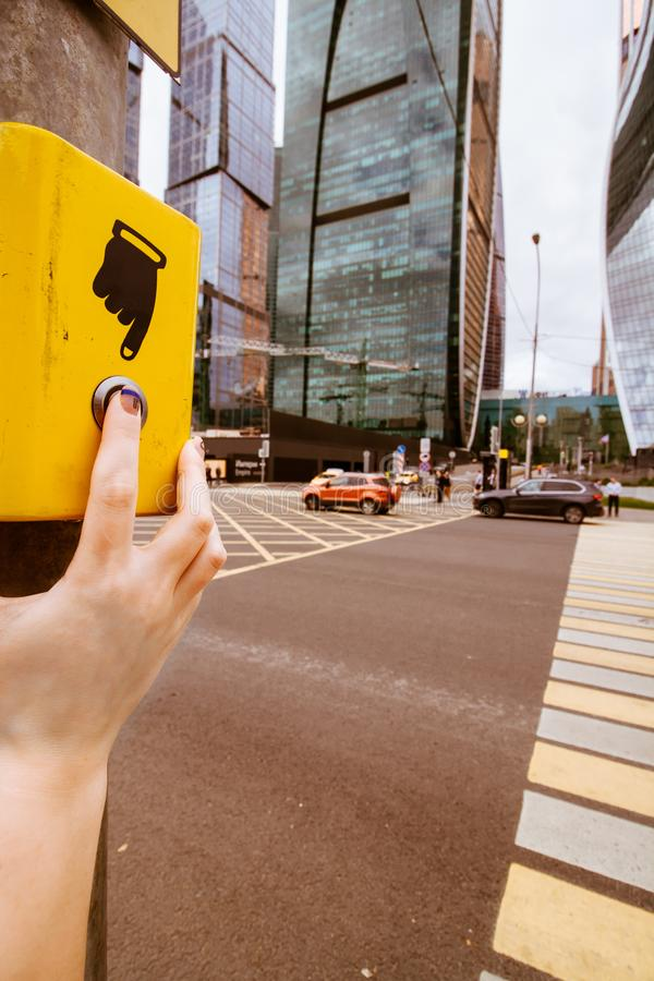 Yellow pedestrian push button and a crossroad stock photo