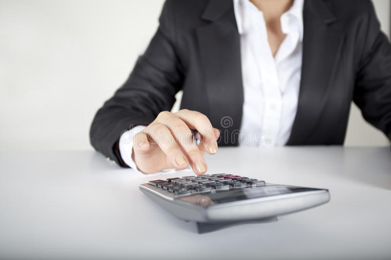 Woman fingers are on the calculator keys-Horizon. Business woman is calculating with calculator royalty free stock image
